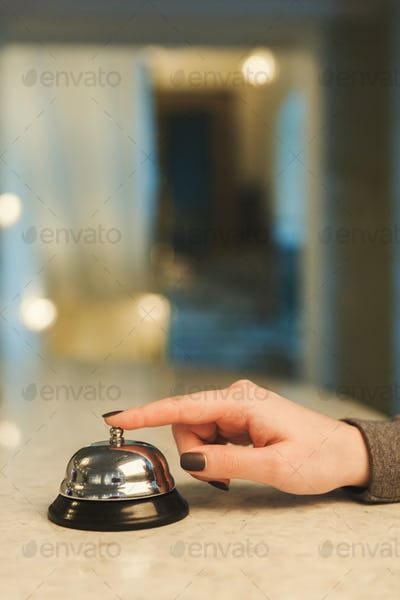 Woman ringing hotel reception service bell closeup