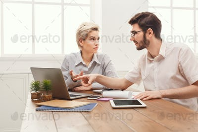 Couple of young business partners working at modern office