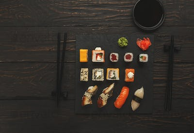 Sushi and rolls set in japanese restaurant on black wood
