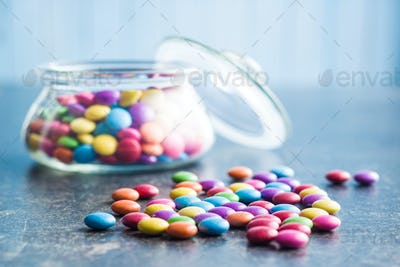 Colorful chocolate candies in jar.
