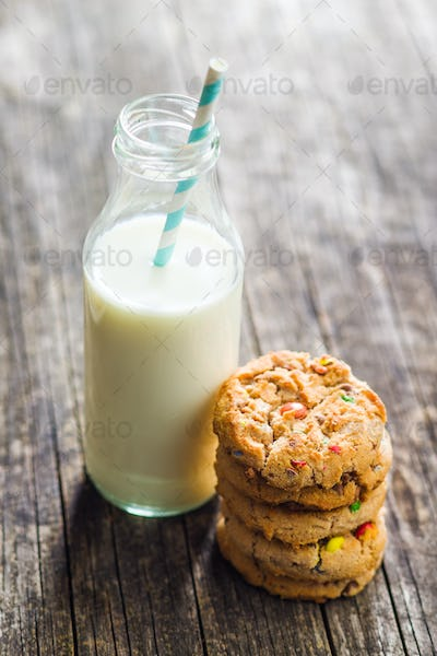 Sweet cookies with colorful candies and milk.
