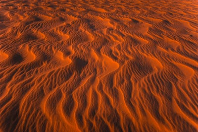 Amazing view of rippled sand dunes texture lit by sunset sun light