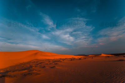 Lonely sand dunes under amazing evening sunset sky