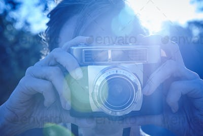 Woman taking pictures with vintage camera. Backlight. Travel background