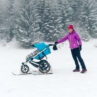 Mother with baby stroller enjoying motherhood in winter forest