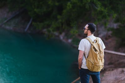Handsome bearded man, with hands in his pockets,looking away standing near lake. Young guy wearing