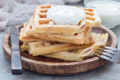 Homemade savory belgian waffles with bacon and shredded cheese, horizontal