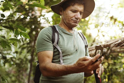 Man using mobile phone in a forest