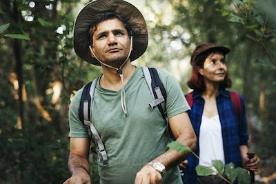 Couple trekking together into the forest