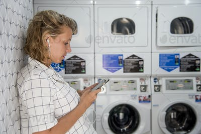 Caucasian woman waiting at the self service laundryomat