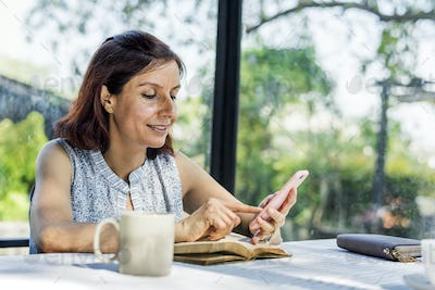 Woman working using mobile phone on an outdoor cafe