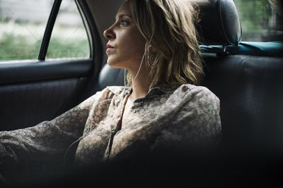 Blond woman sitting in a taxi