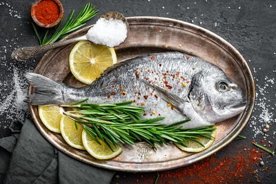 Fresh raw dorado fish with ingredients for cooking. Top view