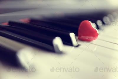Red heart on piano keys