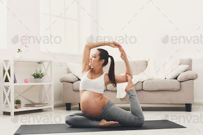 Happy pregnant woman training yoga in camel pose