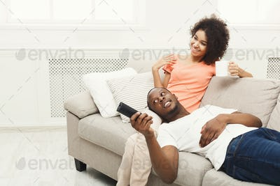 Smiling african-american young couple watching TV at home