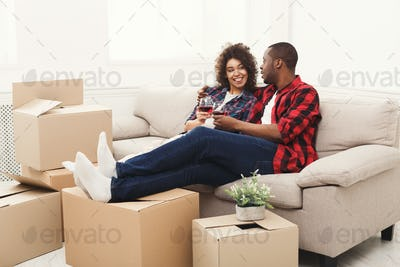 Young balck couple unpacking moving boxes and drinking wine