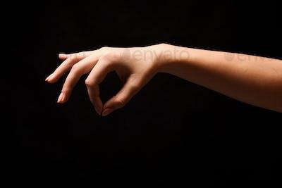 Female hand picking up something, cutout at black