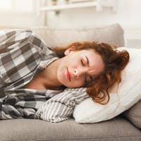 Young girl suffering from stomachache lying down on sofa