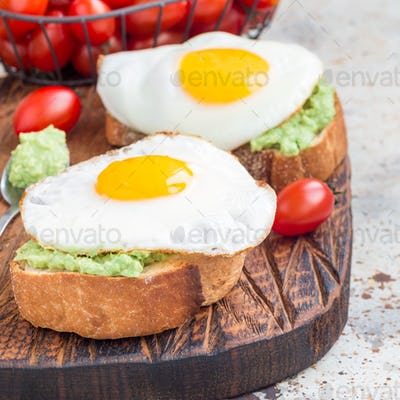 Open sandwiches with mashed avocado and fried egg on toasted bread, square