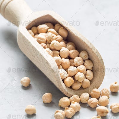 Uncooked dry chickpeas in wooden scoop, closeup, square