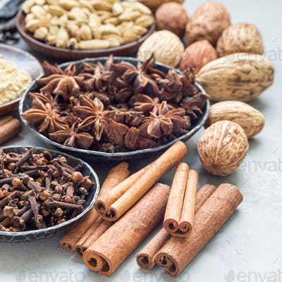 Different kinds of aromatic winter spices in bowls and on a gray concrete background, square