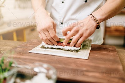 Male cook making seafood, asian kitchen
