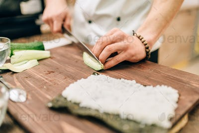 Male cook making sushi rolls on the kitchen