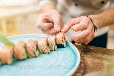Male person cooking sushi rolls, japanese food