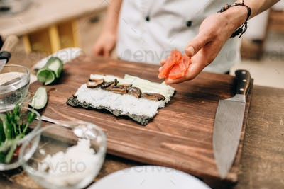 Male cook making sushi on wooden table, asian food