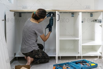 Young woman using electric screwdriver to installation