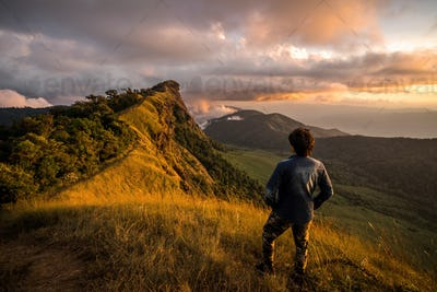 Young traveler looking at beautiful sunrise over the mountain