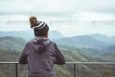 Lonely woman standing absent minded and looking at the mountain