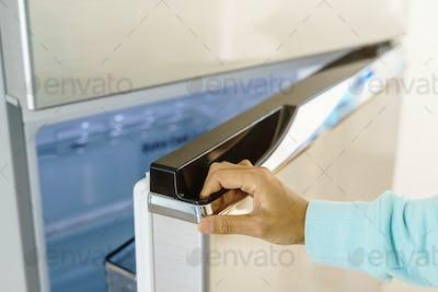young woman hand opening refrigerator door