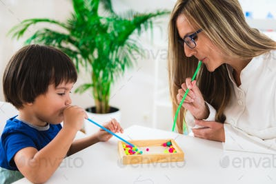 Child psychology, little boy blowing beads with straw