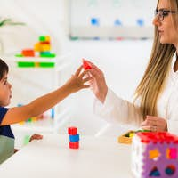 Child psychology, little boy making tower with blocks