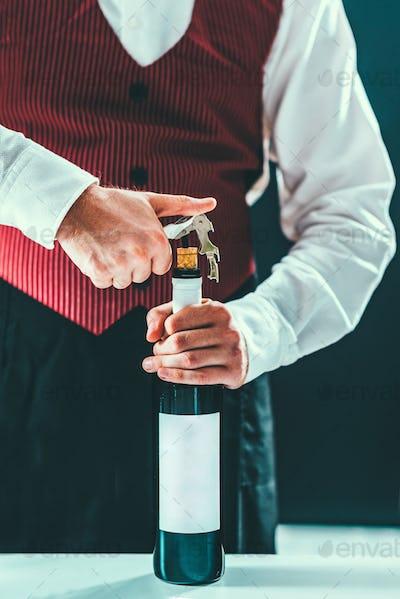 Sommelier opening wine bottle