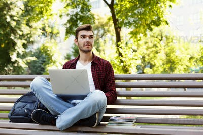 Concentrated man working on his laptop outdoors