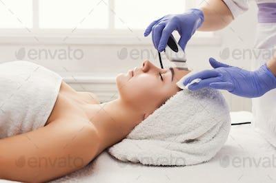 Woman getting facial treatment at beauty salon