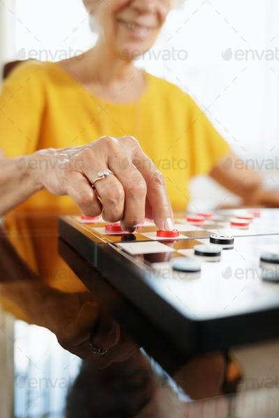 Grandma Playing Checkers Board Game In Hospice