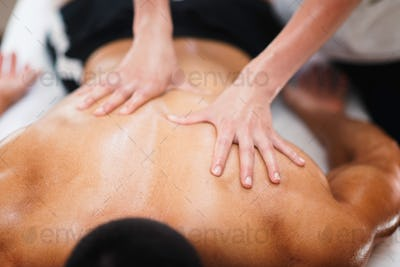 Sports massage. Physical therapist massaging athlete's back