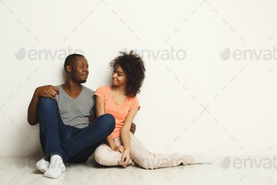 African-american couple looking up, sitting on floor