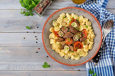 Fried chicken liver with tomato and garnish of pasta. Top view