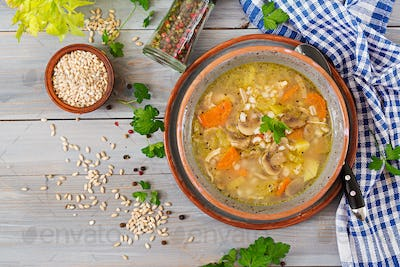 Thick soup with pearl barley, celery, chicken, and mushrooms. Dietary menu. Top view