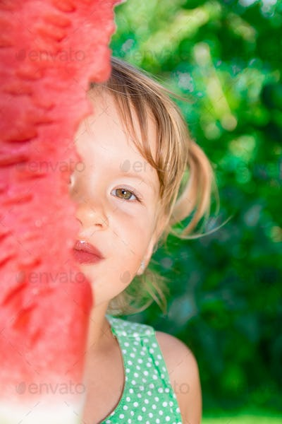 Little girl hide her face by big slice watermelon.