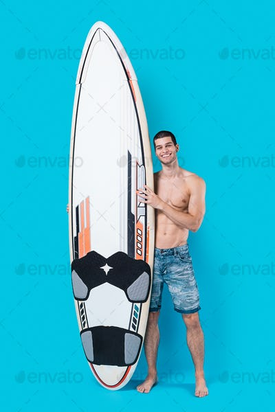 Smiling surfer holding a surfboard
