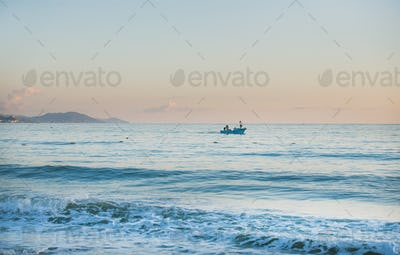 Calm Mediterranean Sea and boat at sunset, pastel colors