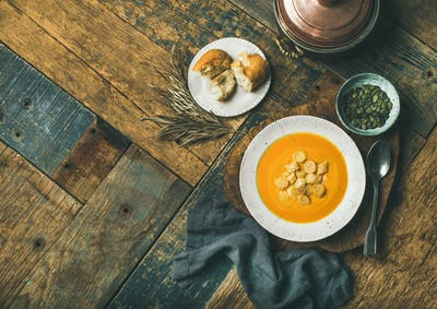 Warming pumpkin cream soup with croutons and seeds, copy space