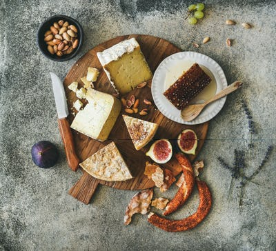 Flat-lay of cheese assortment, figs, honey, bread and nuts