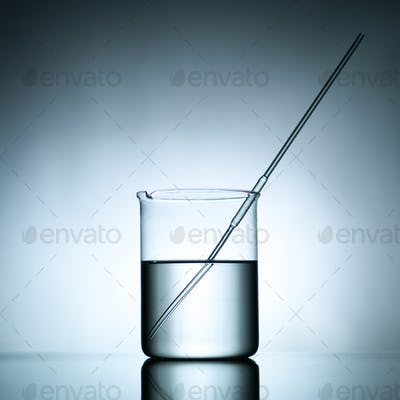 beaker with dropper and transparent liquid substance